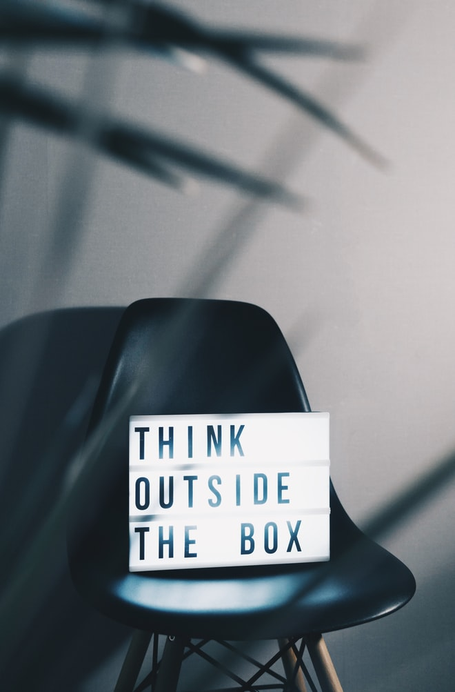 "A chair with a sign that says ""Think Outside the Box"""