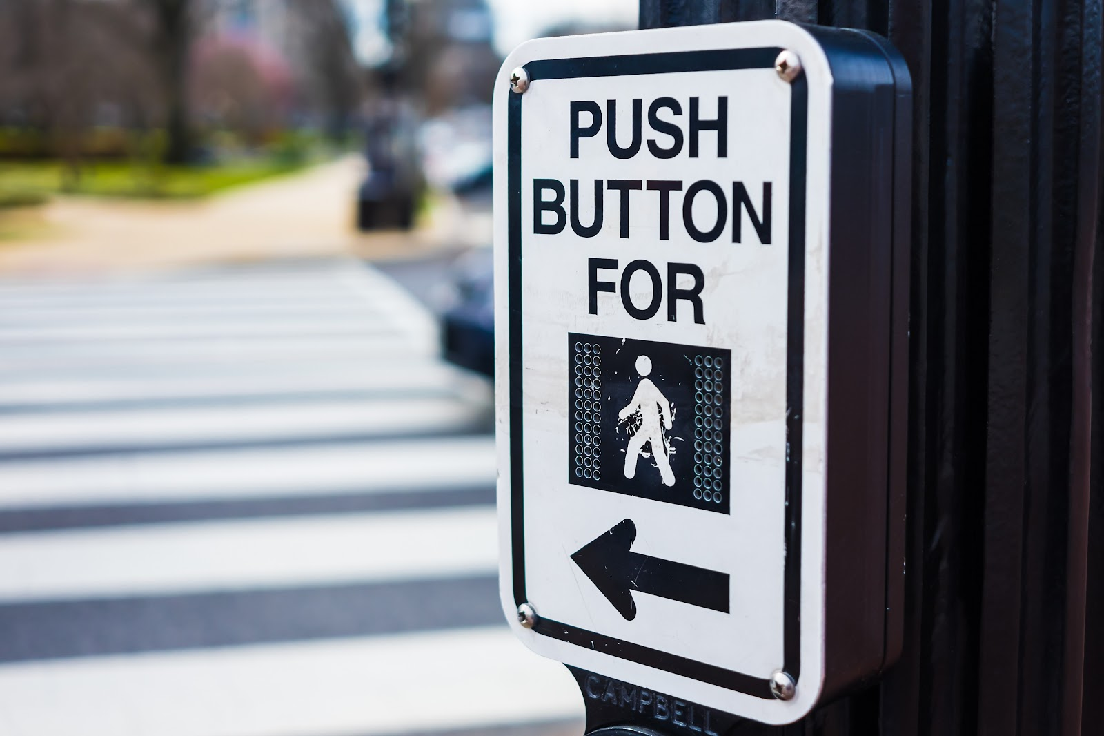 A crosswalk signal sign prompts pedestrians to push the button to activate the signal.