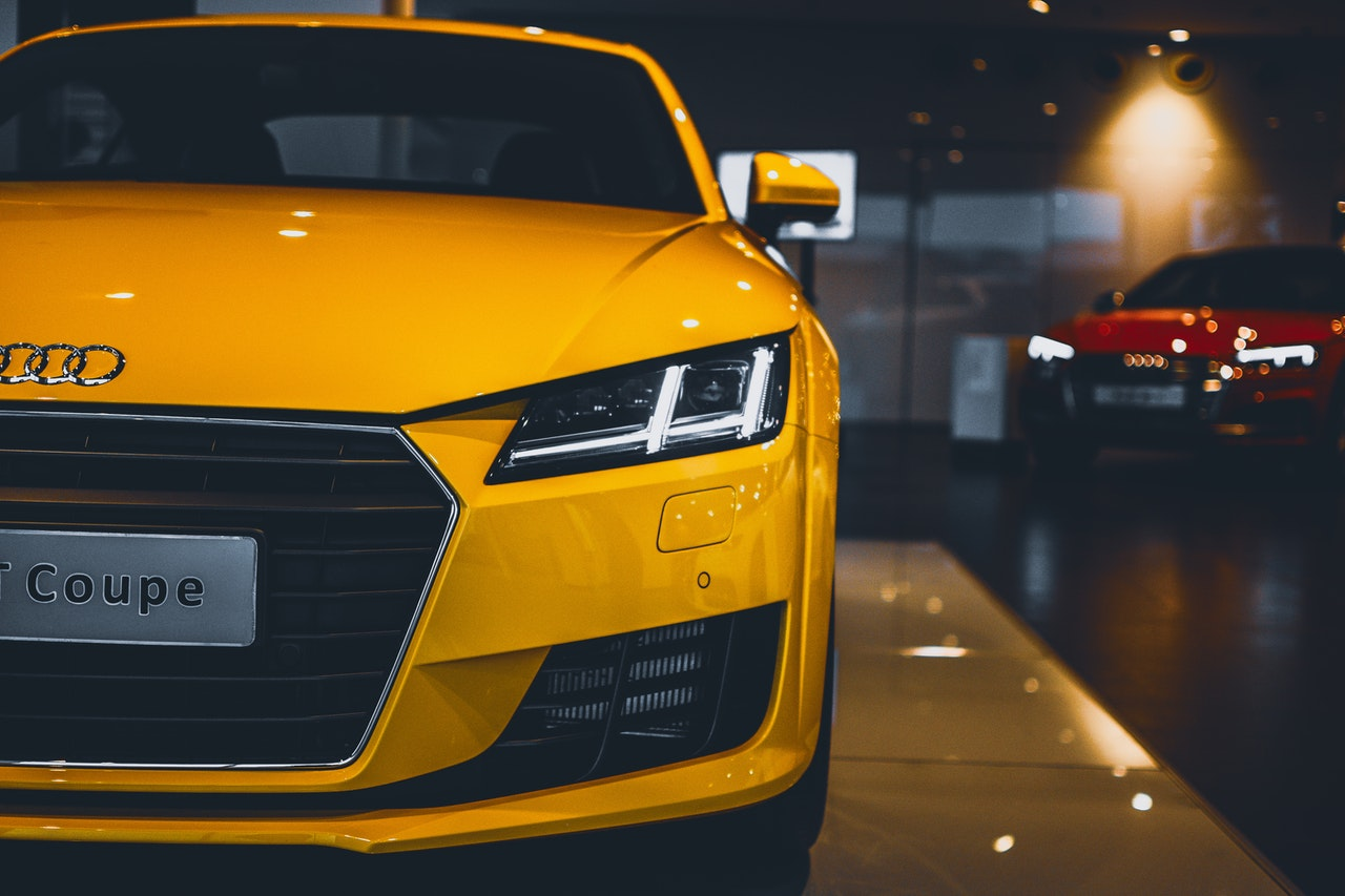 Front view of yellow Audi Coupe on display in a dealership with red Audi in the background