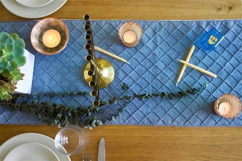 Overhead view of a table set for Hanukkah with menorah, candles, table runner and dishes