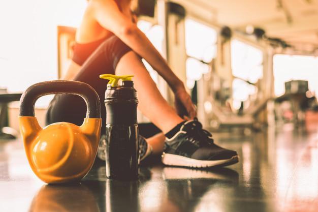 Cima, kettlebells, com, mulher, exercício, malhação, em, ginásio, aptidão, quebrar, relaxe, após, desporto Foto Premium