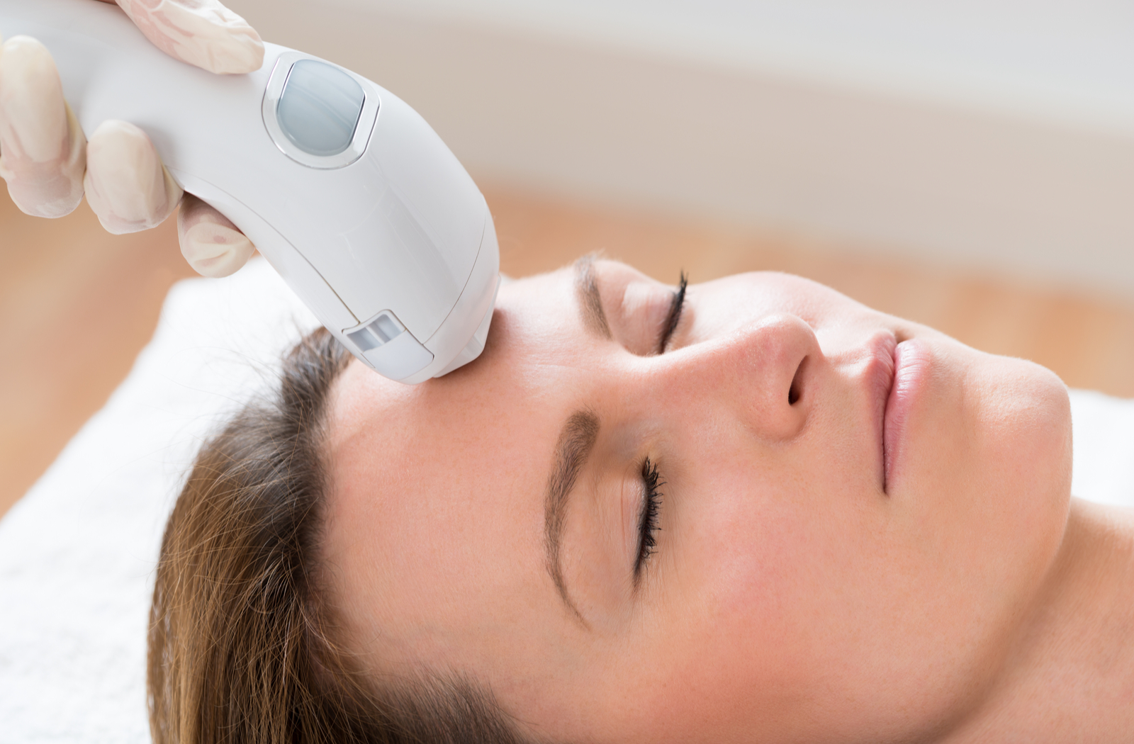 Young women receiving IPL treatment near forehead area