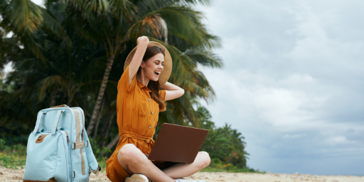 A happy woman working on her laptop on the beach