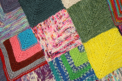close up of knitted square blanket, a pink speckled square is right in the centre