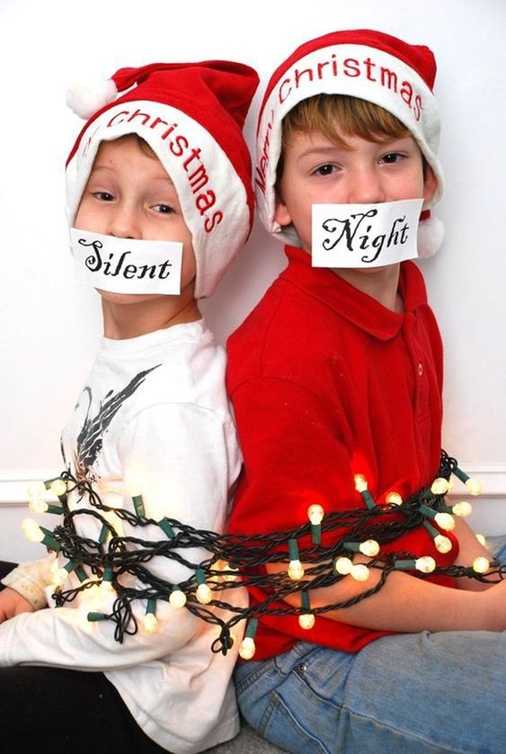 fun christmas card pose of kids in santa hats with christmas lights