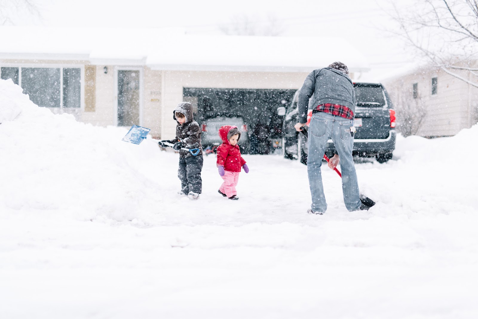 Father shoveling winter snow in his driveway