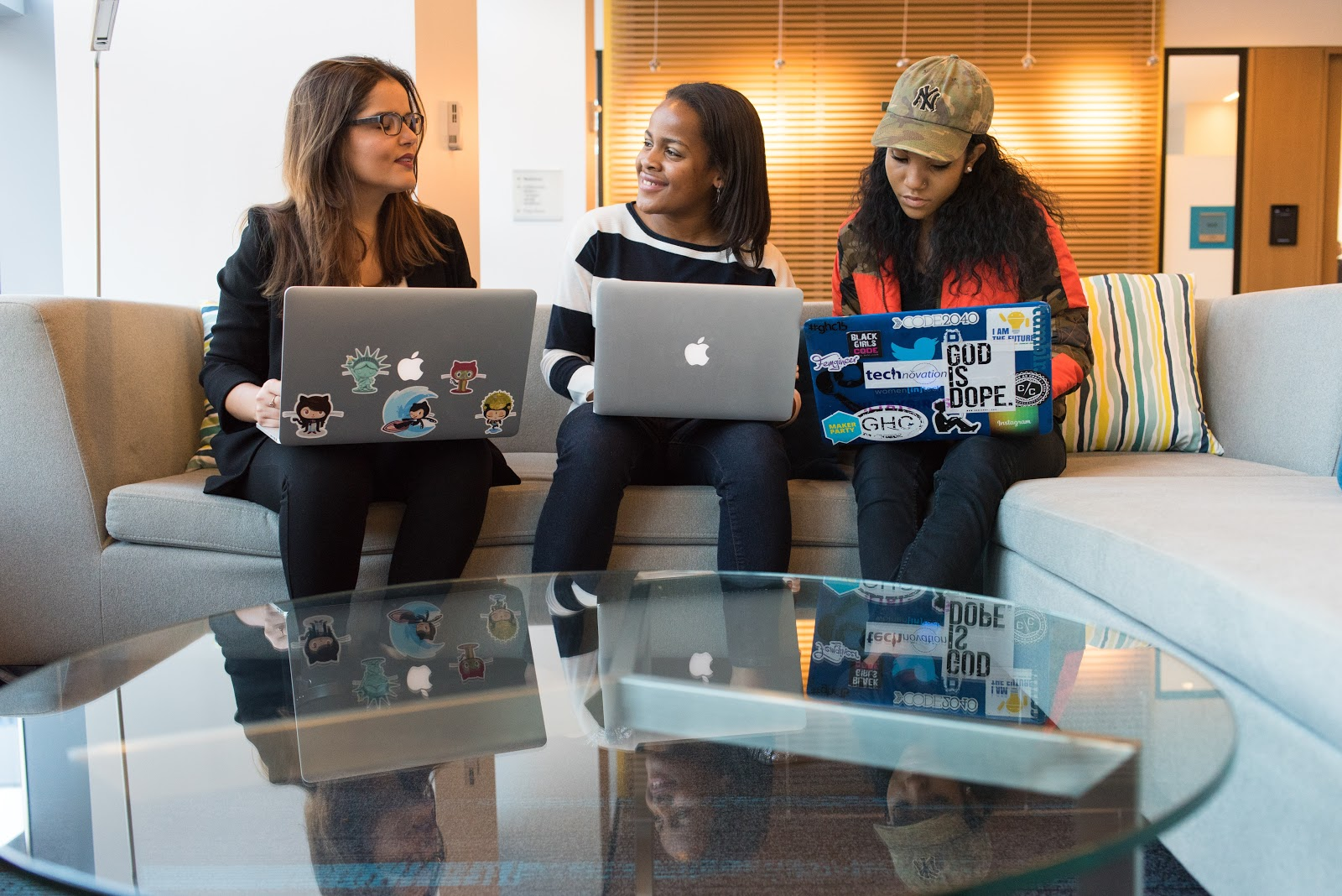 Three women sit on a couch together with their laptops open