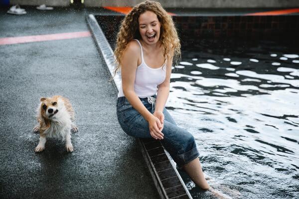 mulher sentada na beira de um lago com um cachorro ao lado