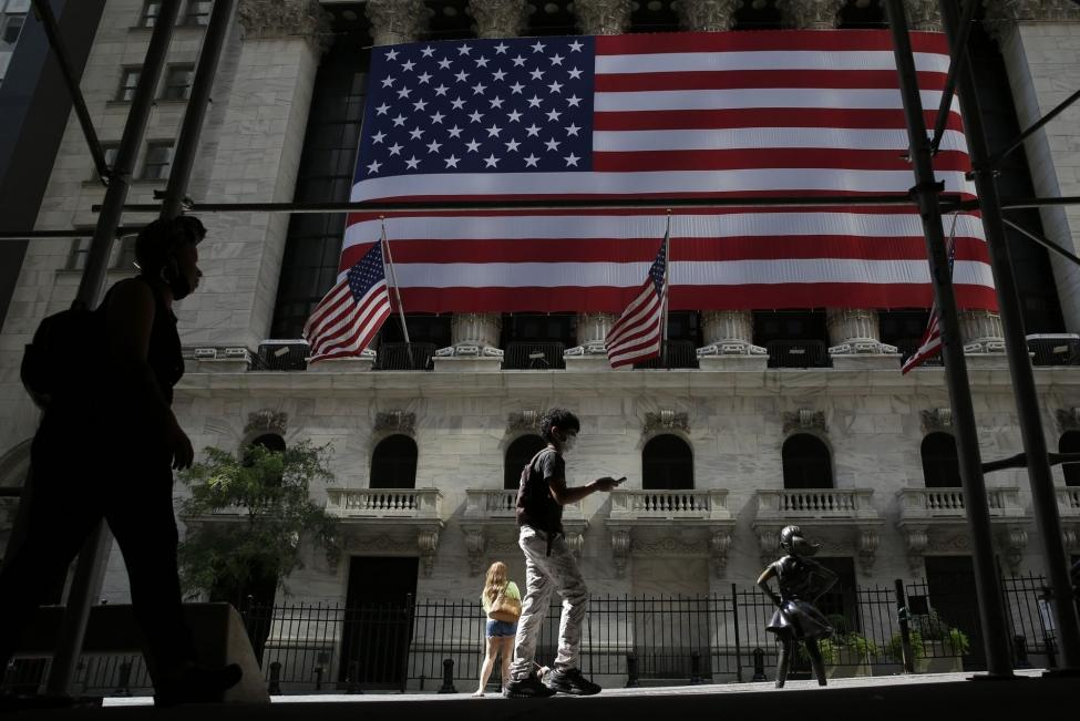 Pedestrians walk past a large American Flag hanging outside of the New York Stock Exchange in New York City on September 8. The Dow finished mostly flat on Wednesday after an outlook by the Federal Reserve that said interest rates will likely remain near zero until at least 2022. Photo by John Angelillo/UPI