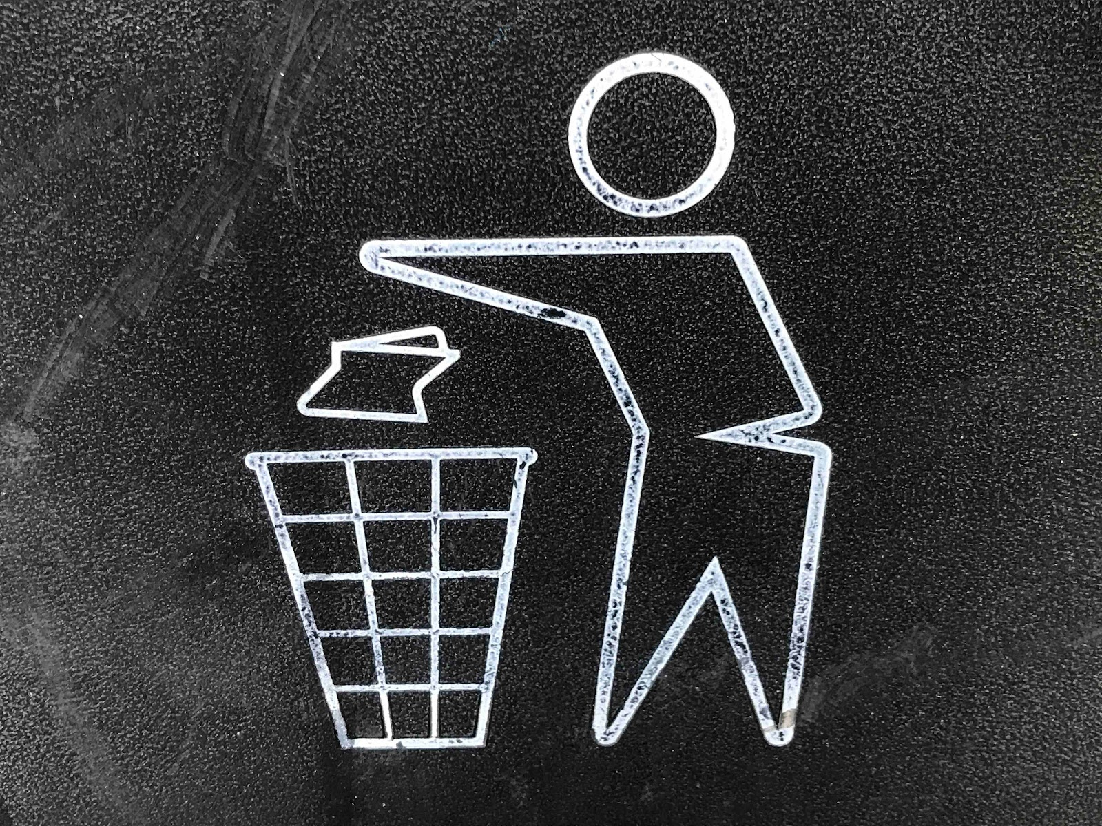 black and white image of a person throwing away a paper into the trash bin