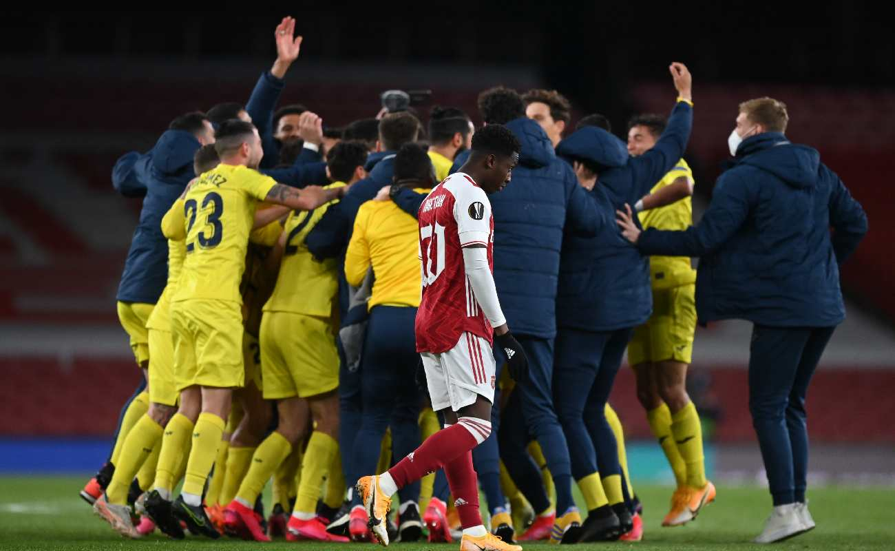 Alt: Villarreal celebrating their win over Arsenal with a dejected Eddie Nketiah of Arsenal walking by. Photo by Shaun Botterill/Getty Images