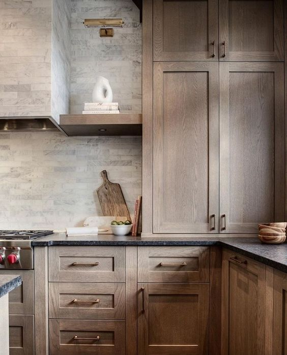 rustic wood shaker cabinets with brass hardware and dark granite countertops. a neutral tile backsplash ties the room's colors together