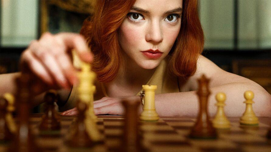Mulher branca ao fundo de cabelos ruivos olhando para a câmera e sua mão em primeiro plano embaçada segurando uma peça de xadrez. Outras peças de xadrez também embaçadas estão no primeiro plano em cima do tabuleiro. Foto: Reprodução Netflix.