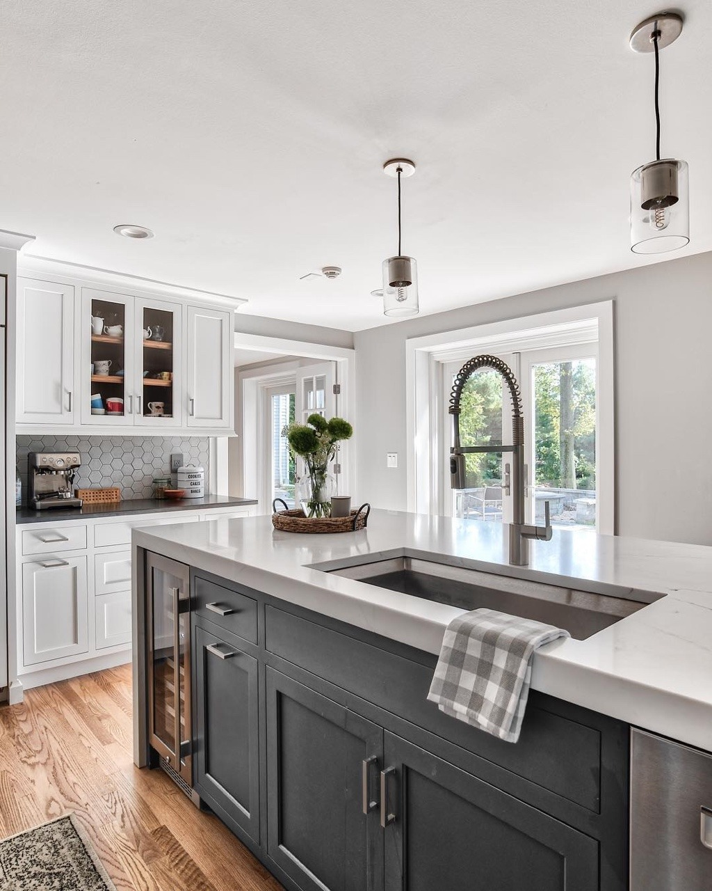 modern farmhouse kitchen with farmhouse sink island, white and grey kitchen cabinets, wood floors and hexagon white backsplash