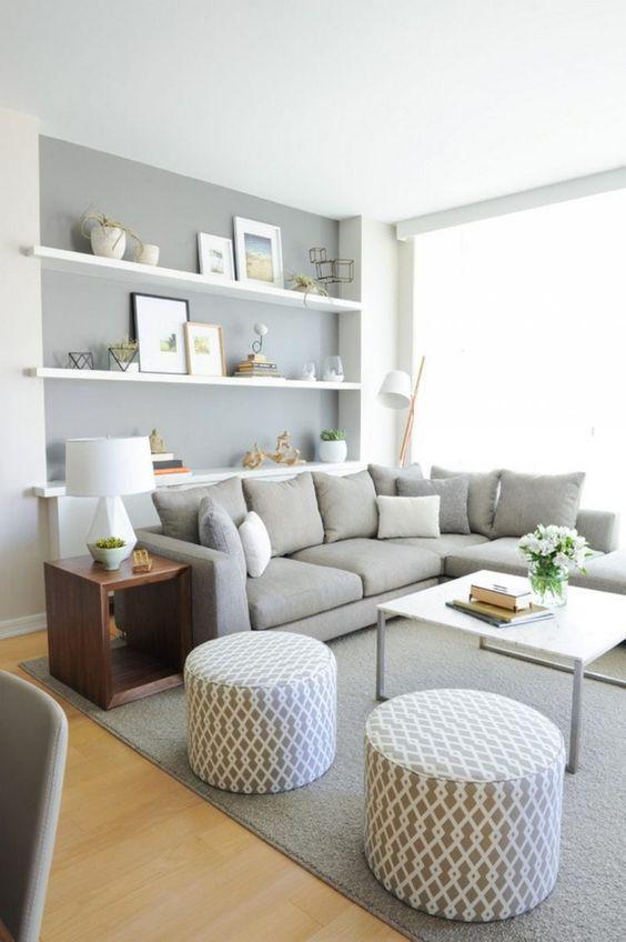 Sala em tons cinza, como sofá e almofadas cinza, prateleiras brancas, quadros e objetos decorativos, mesa de centro branca e puff cinza.
