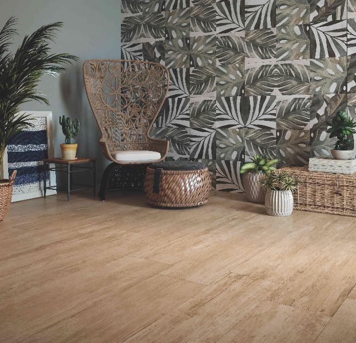 ambiente com piso de madeira, papel de parede de folhas de plantas, cadeira de madeira com estofado, cestas de palhas e vasos de plantas.