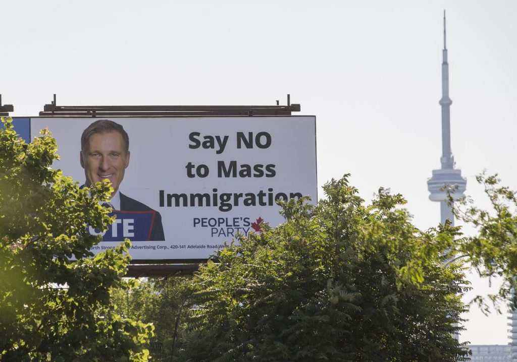 "A People's Party of Canada billboard with the party leader Maxime Bernier and the message 'Say NO to Mass Immigration""."
