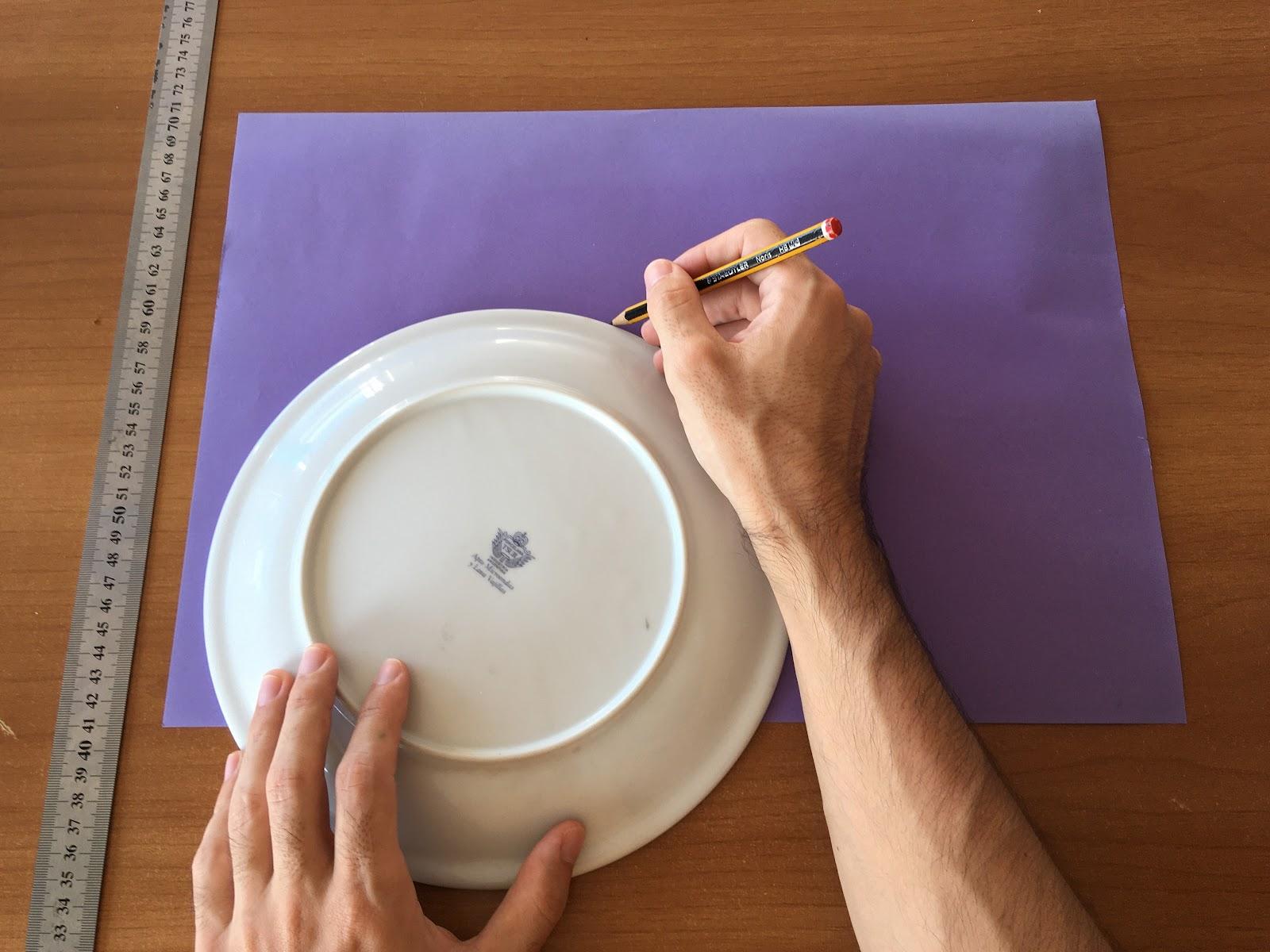 Trazado de un arco en lápiz sobre la cartulina de color utilizando el contorno de un plato.