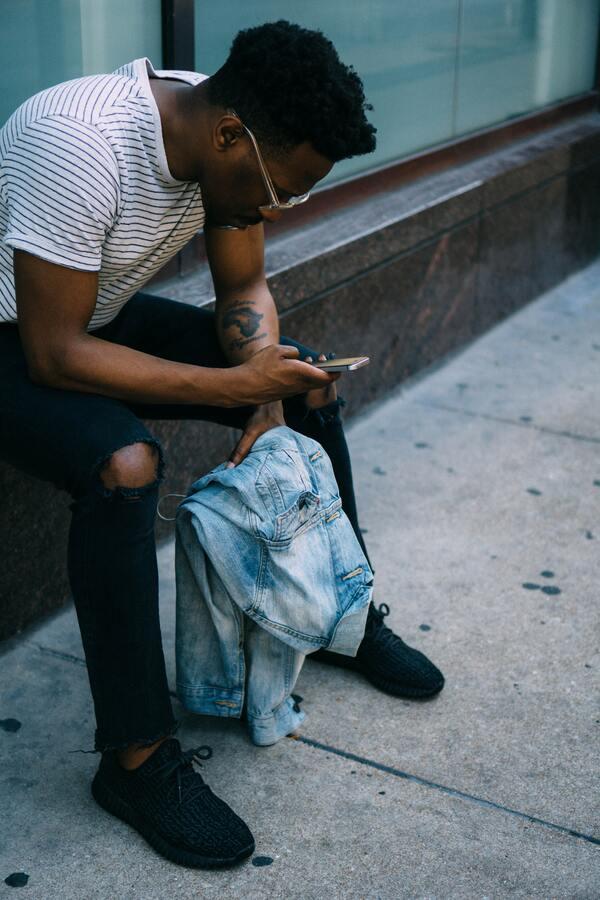 Foto de um homem negro na rua, sentado, segurando uma camisa jeans e mexendo no celular