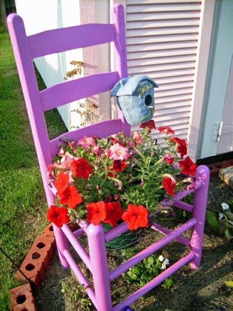Image d'une chaise repeinte avec un pot de fleur à l'intérieur.