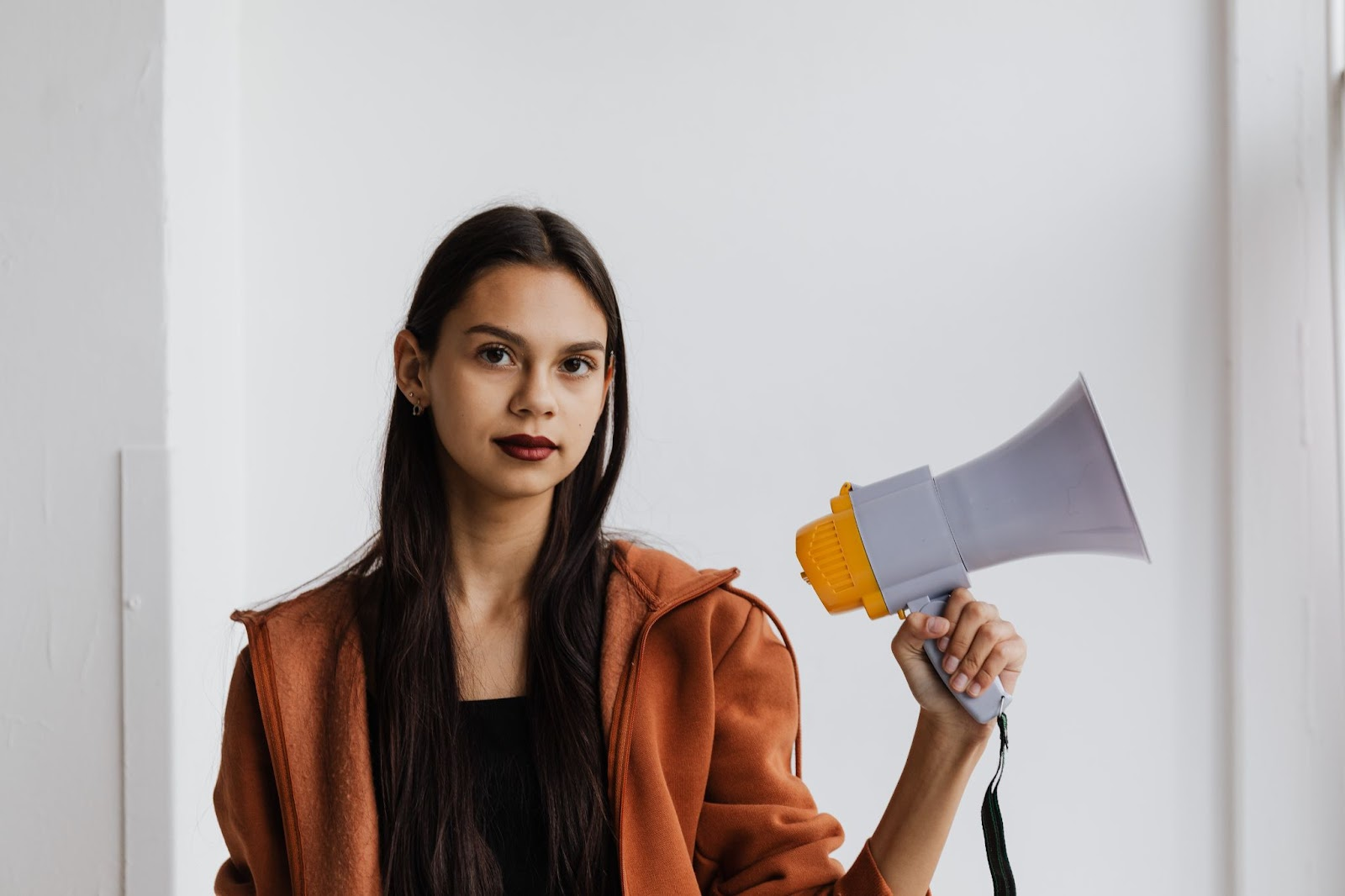 A woman holding a megaphone looks calmly and purposely at the viewer.