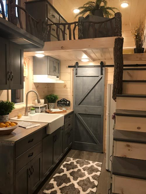 rustic tiny house kitchen with dark wood shaker cabinets, sliding barn door, wood floors, wood paneling and farmhouse sink. rustic tiny home, tiny home cabin, tiny house cabin decor