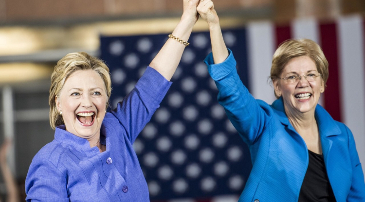 Elizabeth Warren and Hillary Clinton clasping hands.