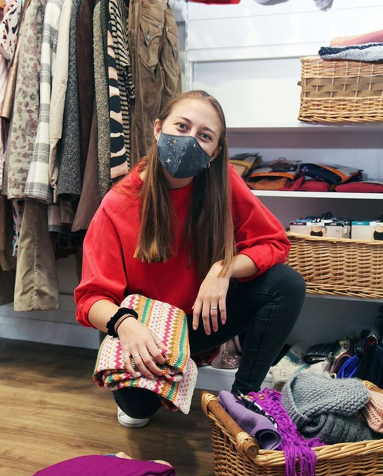 Image of a volunteer tidying scarves and hats away in a charity shop.
