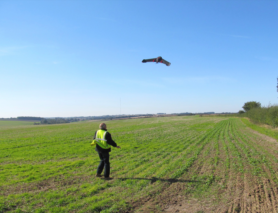 A drone pilot working for Hummingbird scans a farmer's field.