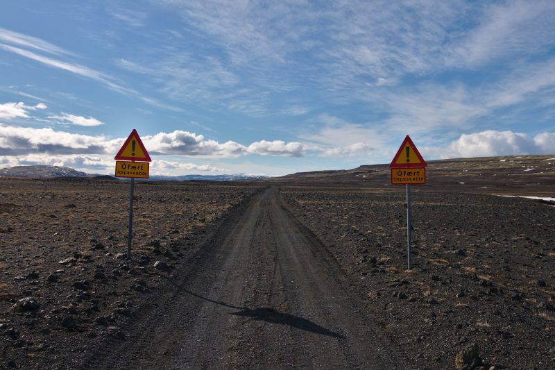 Dirt road with the warning signs saying Impassable.