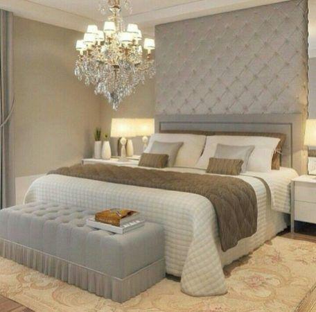 Quarto de casal luxuoso com cabeceira estofada até o teto prata, lustre de cristal pendente e puff no pé da cama.