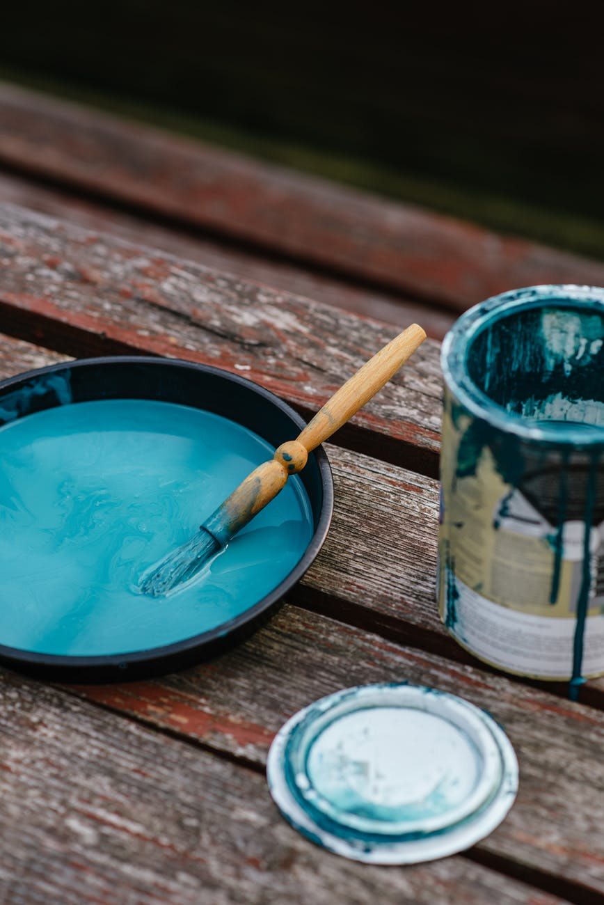 Open can of blue paint with a paint brush on wood planks.
