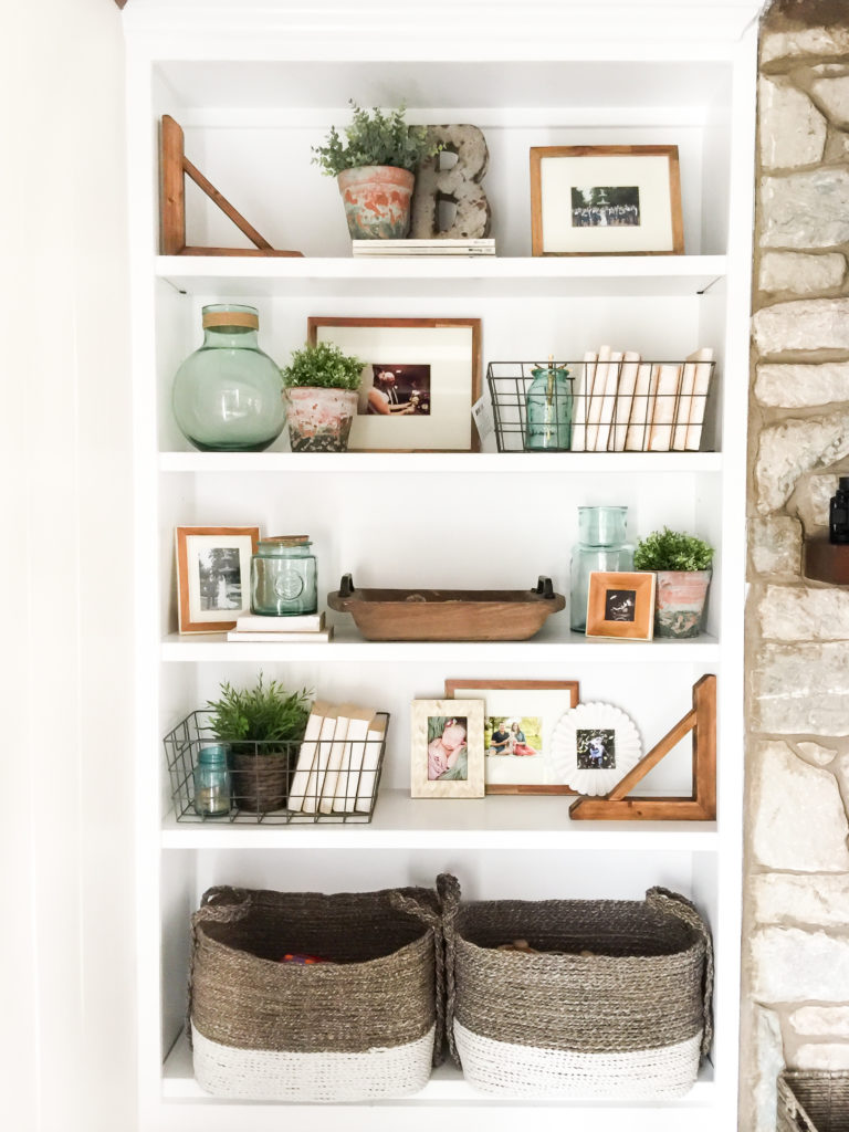 A white bookshelf that features lots of wooden and brown toned decor.