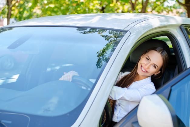Mulher sorrindo de dentro do carro