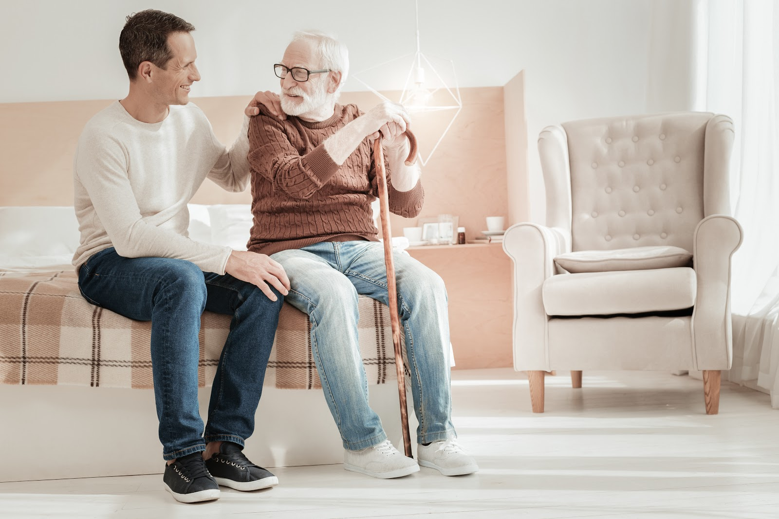 A man and his elderly father sitting and smiling together