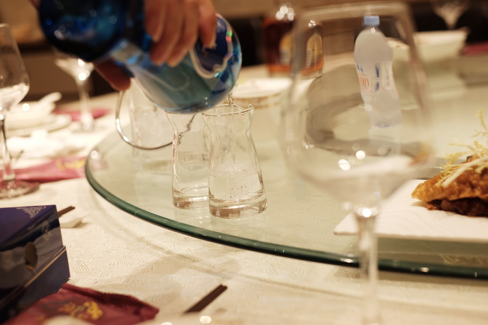 A Chinese dining table with strong spirit being poured into small glasses.