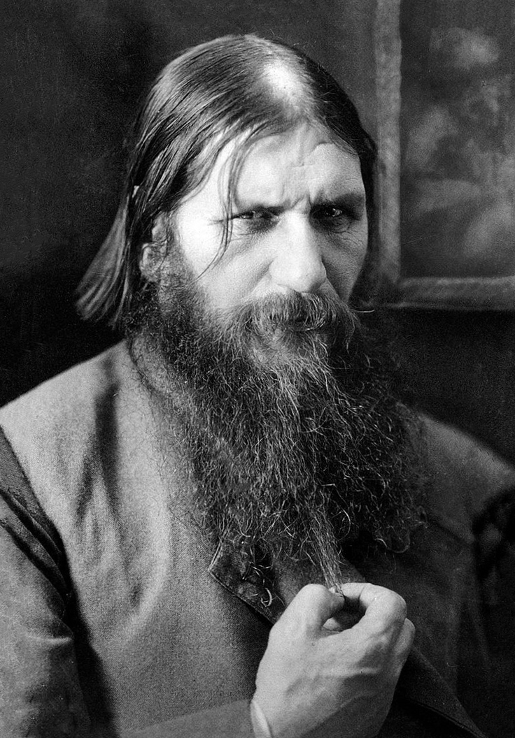 Photograph of Rasputin, glaring at the viewer and holding the end of his long beard.