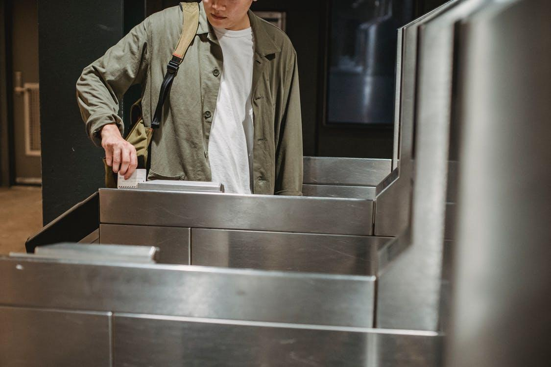 Crop unrecognizable male passenger in casual clothes with backpack inserting ticket in entrance machine of automated gate while entering modern subway station