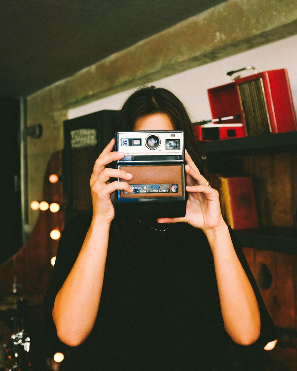 woman in black shirt holding black and gray polaroid instant camera