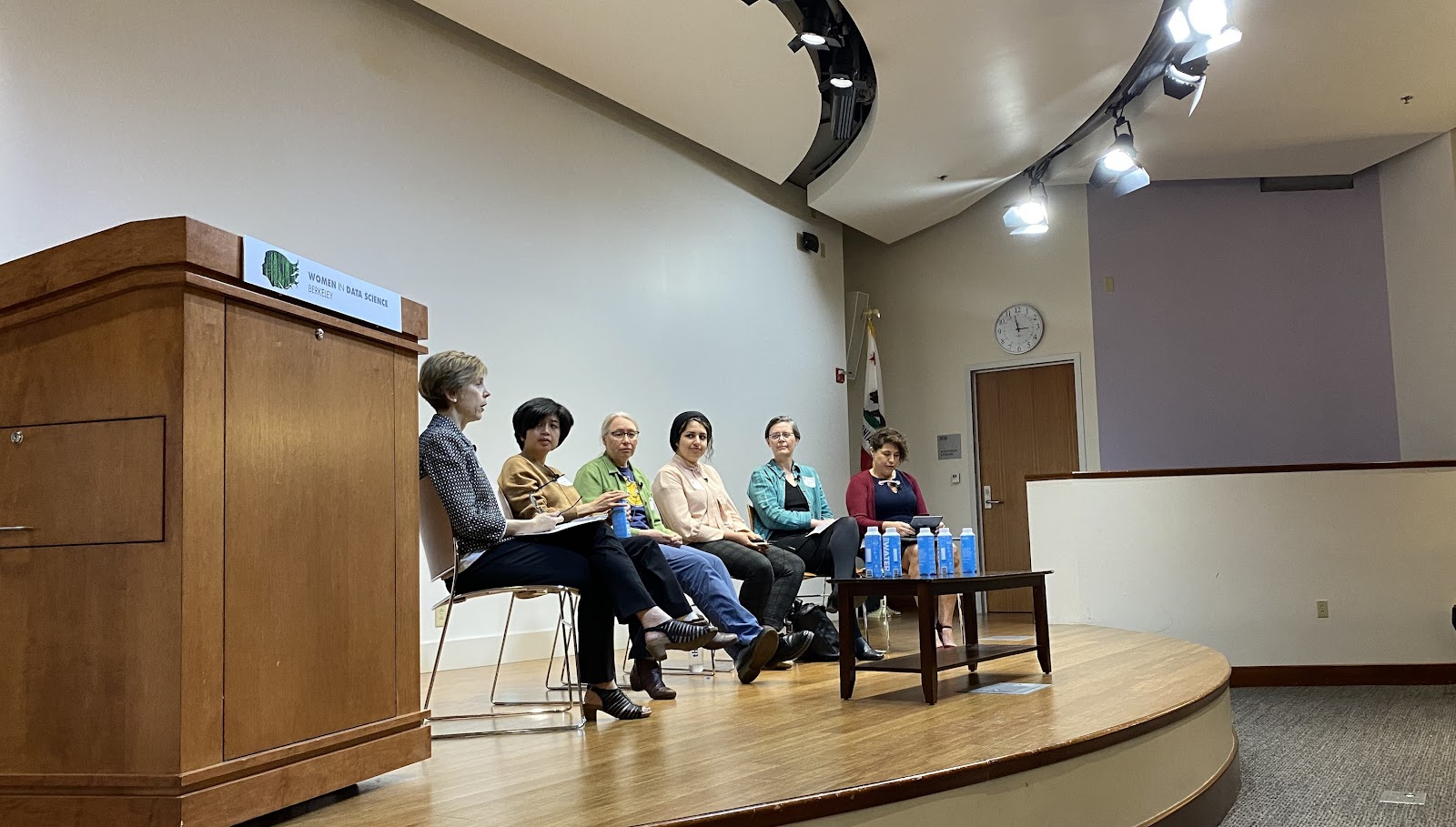 Panelists for the Building Inclusive Data Communities Panel at the 2020 WiDS Berkeley Conference are seated on a stage discussing a topic. Panelists pictured from left to right: Dr. Camille Crittenden (Moderator), Ling Cheng, Annette M. Grenier, Prof. Niloufar Salehi, Prof. Cathryn Carson, Dr. Claudia von Vacano
