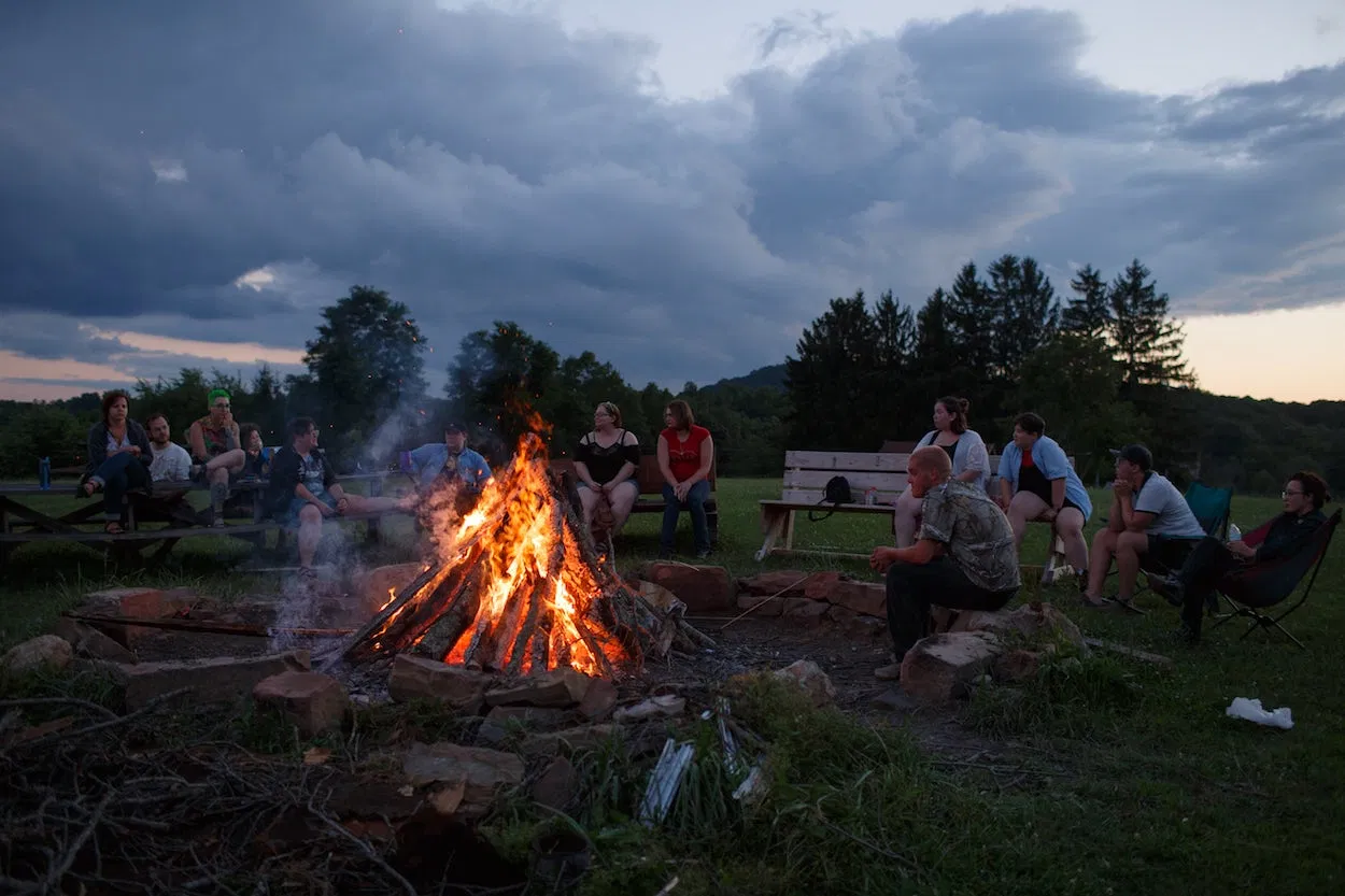 In this picture, a group of people are gathered around a bonfire in an open field lined with trees at dusk.