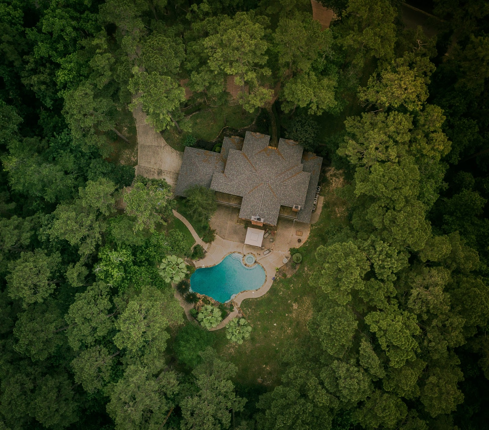 Aerial view of a house in a heavily wooded area