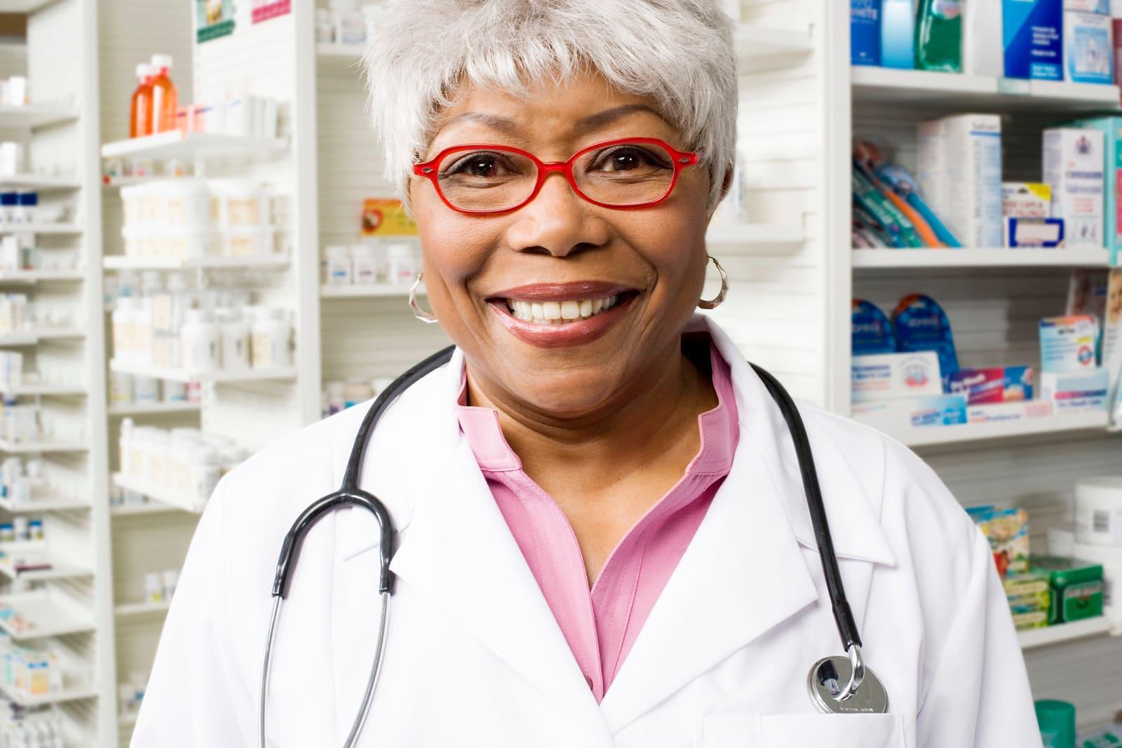 A imagem mostra uma operadora de caixa de farmácia sorrindo para a foto.