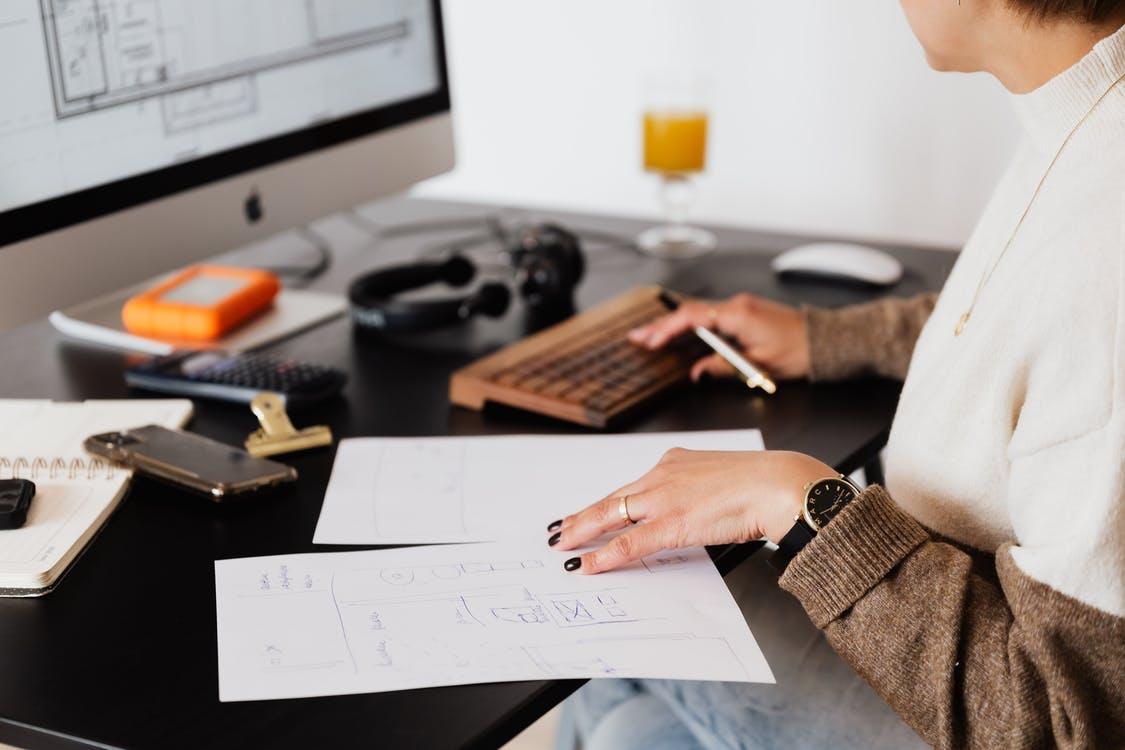 Side view of crop faceless female entrepreneur checking document and typing on keyboard of computer during work in office