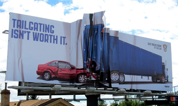 "Billboards that looks torn in the middle with a car hitting a truck and the message ""Tailgating isn't worth it"""