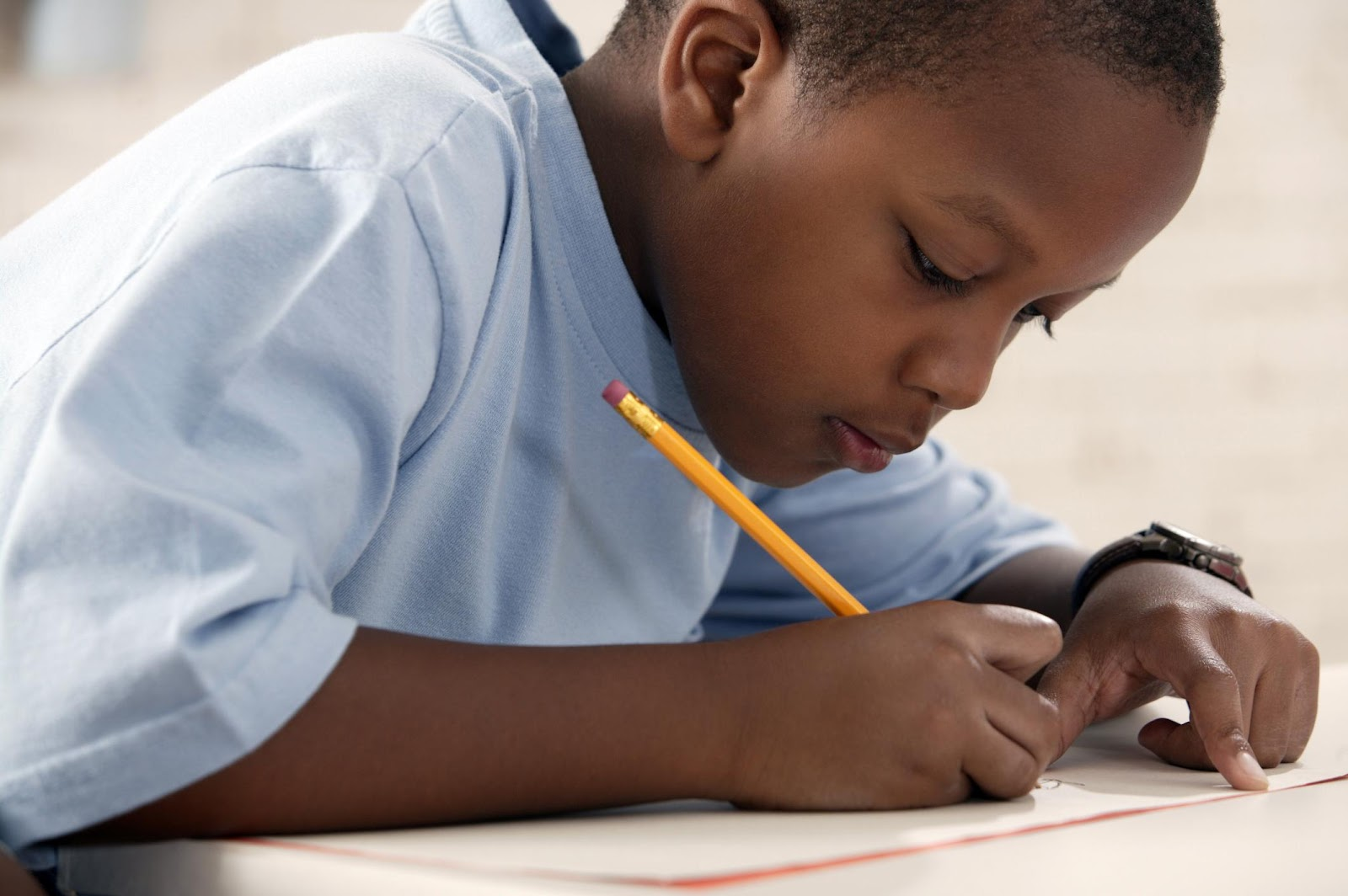 Boy writing with a pencil