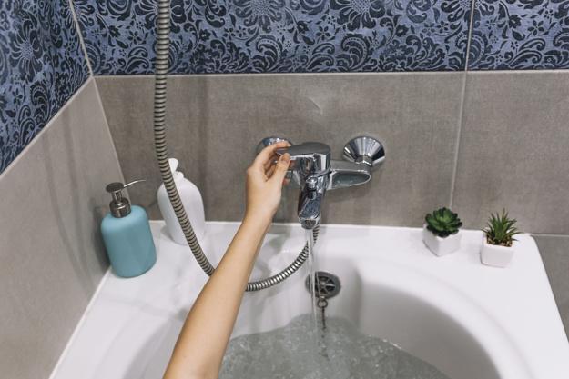 Crop hand touching bath tap Free Photo