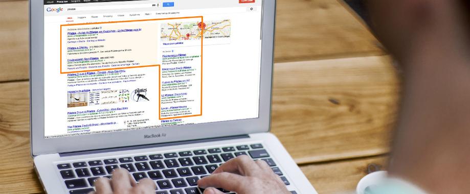 Imagem com uma pessoa mexendo em seu laptop. Em seu laptop está aberta a página da google em uma pesquisa, e nesta pagina está aparecendo alguns anúncios da Google Ads de sites relacionados ao tema pesquisado.