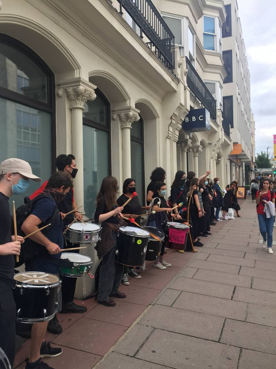 Photo of protesters drumming in the streets of Brighton