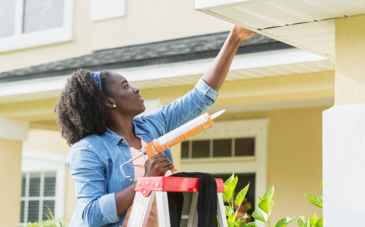 A woman using a caulk gun on the outside or her house
